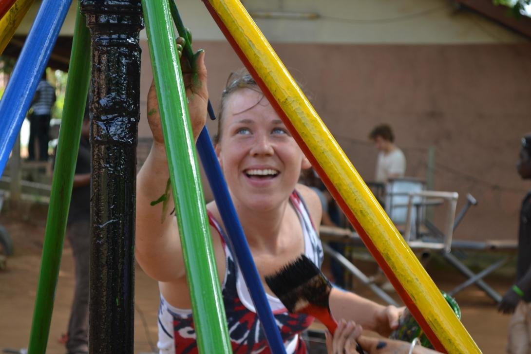 A volunteer paints a playground as part of her construction volunteering in Ghana